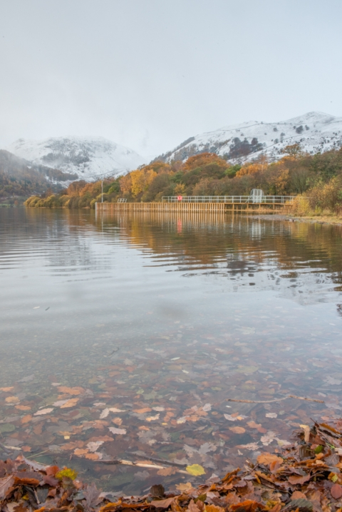 The pier with snow capped mountains in the background and autumnal leaves in the foreground